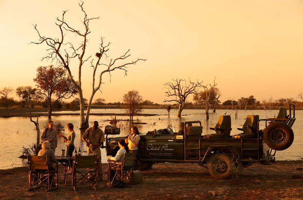 Sundowner drinks in the vast South African wilderness.