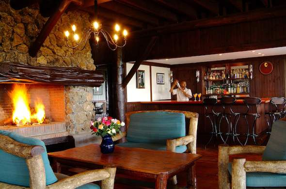 Snuggle up next to the fireplace in the guest lounge of Great Rift Valley Lodge.
