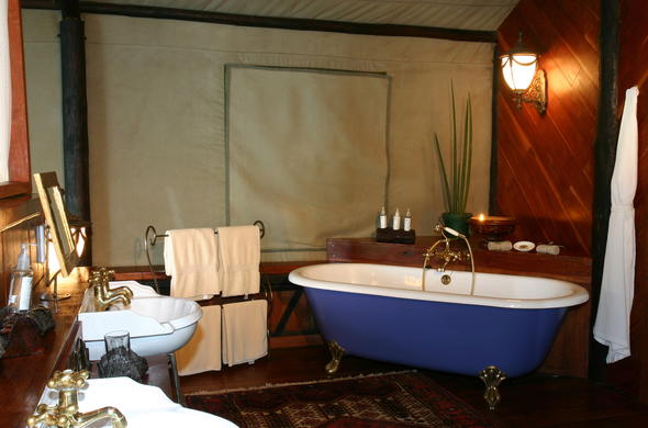 Luxurious tented bathroom with ball-and-claw bath and double basin.
