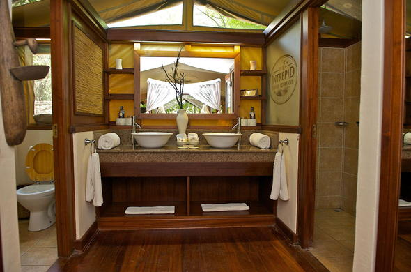 Bathroom with flush toilet,shower and his and her vanity.