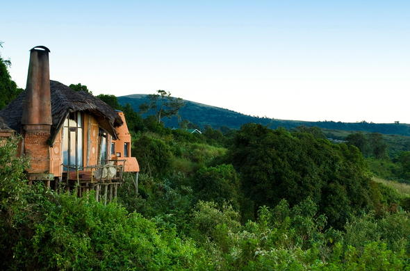 Ngorongoro Crater Lodge is located among lush green vegetation.